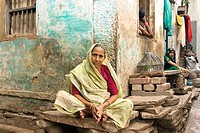 A woman sitting on the stone where she does her laundry in the old city of Varanasi in Uttar Pradesh