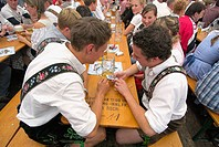 Young men with traditional Bavarian costume at Oktoberfest beer tent. Munich, Bavaria, Germany