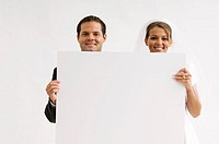 Bride and groom holding blank sign