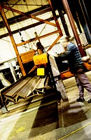 Factory worker moving iron beams