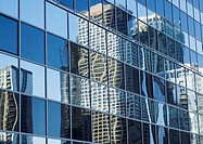 Skycrapers reflected on glass facade, low angle view