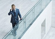 Businessman leaning on railing, using cell phone, high angle view