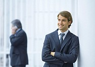 Businessman leaning against column, smiling