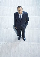 Businessman standing with briefcase, high angle view
