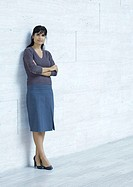 Businesswoman standing, leaning against wall, full length