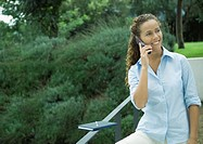 Woman using cell phone outdoors, agenda balanced on railing