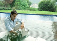 Casually dressed young executive working near edge of pool