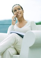 Woman sitting in armchair, using cell phone