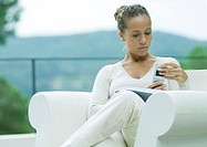 Woman sitting in armchair, outdoors, using cell phone