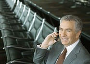 Businessman using cell phone in airport lounge