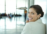 Woman looking over shoulder at camera, in airport