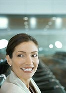Woman in airport lounge, smiling over shoulder
