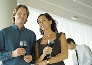 Man and woman chatting and holding glasses of wine