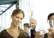 Woman holding up glass of champagne, smiling at camera