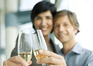 Man and woman clinking champagne glasses, focus on glasses in foreground