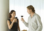 Man and woman standing with glasses of red wine, chatting