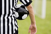Mid section view of a referee with a soccer ball under his arm