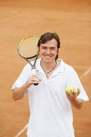 Portrait of a mid adult man holding tennis balls and a tennis racket