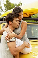 Young woman sitting on the bonnet of a jeep and embracing a mid adult man