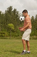 Side profile of a mid adult man playing with a soccer ball