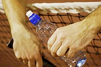 Close-up of a person's hand holding a water bottle