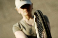 Close-up of a mid adult woman holding a tennis racket
