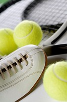 Close-up of a tennis shoe with tennis balls and rackets