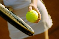 Mid section view of a woman holding a tennis racket and a tennis ball