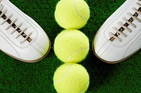 High angle view of a pair of sports shoes and three tennis balls