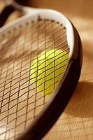 Close-up of a tennis racket and a tennis ball