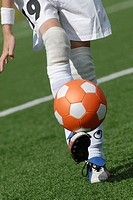 Low section view of a soccer player balancing a soccer ball