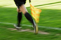 Low section view of a linesman running with a flag