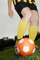 Low section view of a soccer player playing with a soccer ball