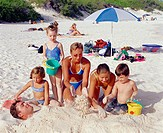 Mid adult woman covering a mid adult man in sand with her three daughters and a son, Bermuda