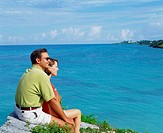 Side profile of a young couple sitting together on a rock, Bermuda (thumbnail)