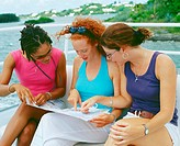 Close-up of three young women sitting on a bench and looking at a map, Bermuda