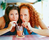 Portrait of two young women drinking juice from a glass with straws, Bermuda