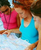 Close-up of three young women sitting and looking at a map, Bermuda