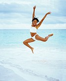 Low angle view of a young woman jumping on the beach, Bermuda