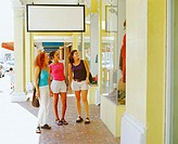 Three young women looking at a window display in a market, Bermuda