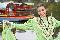Portrait of a young woman standing by the lake and smiling