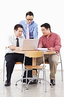 Three businessmen discussing in front of a laptop