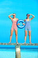 Two women in old fashioned bathing suits holding inner tube at beach