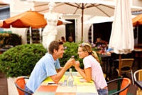 Couple holding hands at outdoor restaurant