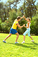 Couple in athletic gear wrestling outdoors
