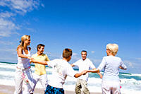 Multi-generational family dancing in circle at beach