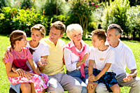 Multi-generational family sitting and talking outdoors