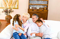 Grandparents hugging grandchildren on sofa