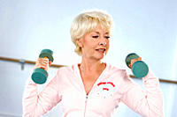 Senior woman using dumbbells indoors