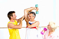 Fitness instructor showing senior couple how to use dumbbells